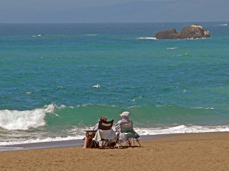 People sit in lounge chairs on the sandy beach in Sonoma County