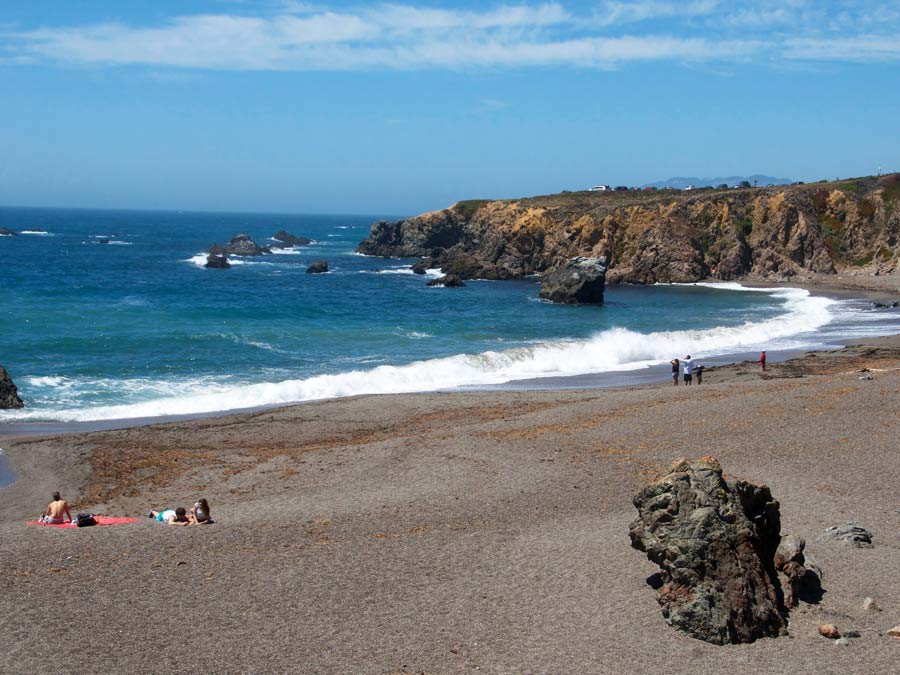 People sit on a blanket on a gravely beach along the Sonoma Coast