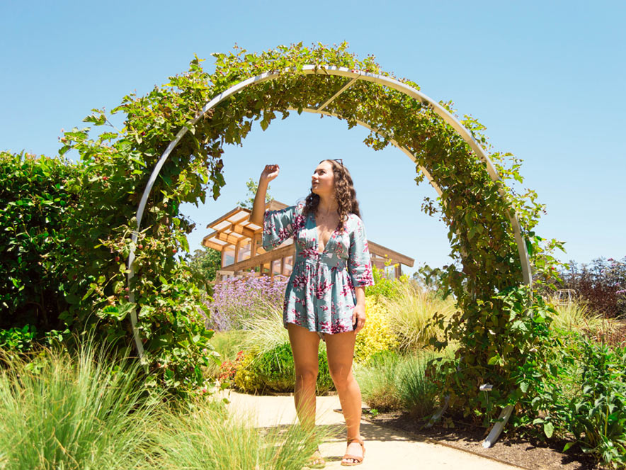 A woman poses for a photo under an arbor of flowers