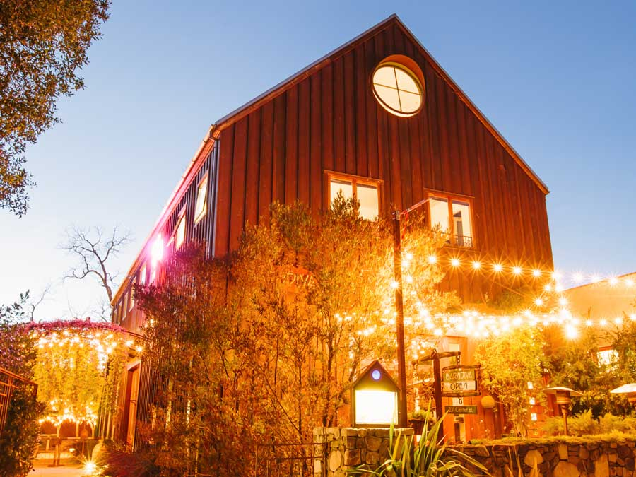 The exterior of the barn is lit up at night in Healdsburg