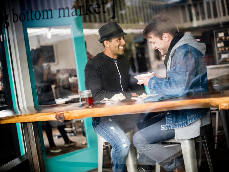 Two men smile and sit at the table that looks out front of the restaurant in Sonoma County