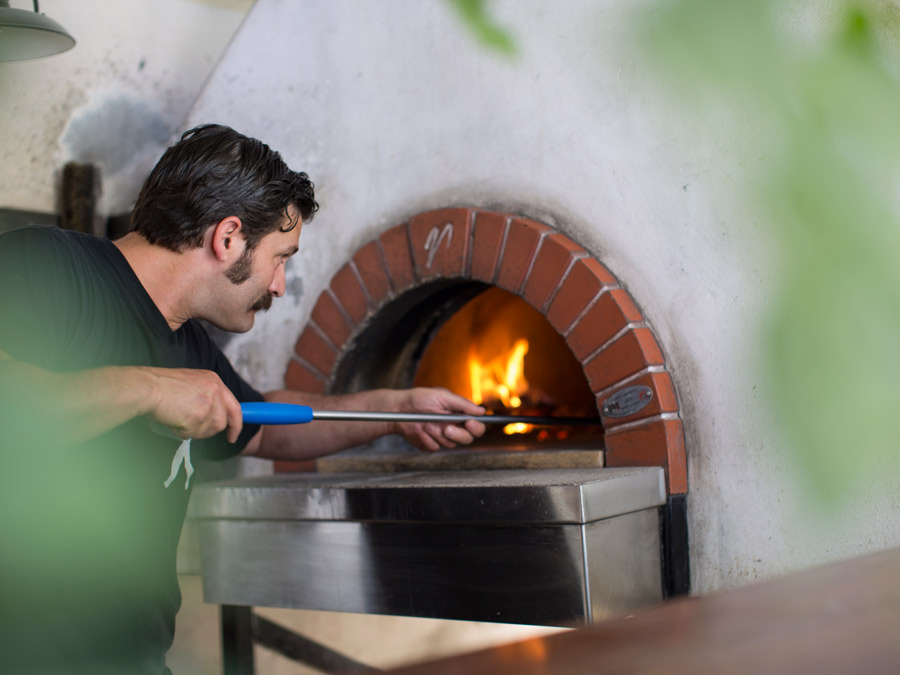 A man with a mustache cooks a pizza in a wood burning oven