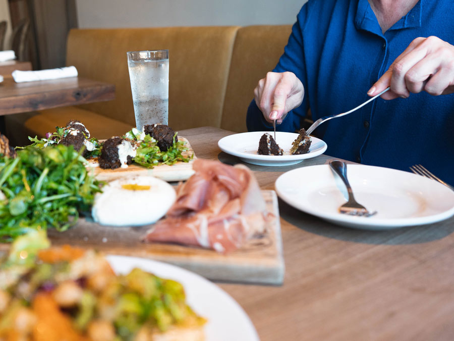 A person eats at a table with burratta and a salad at Catelli's in Sonoma County
