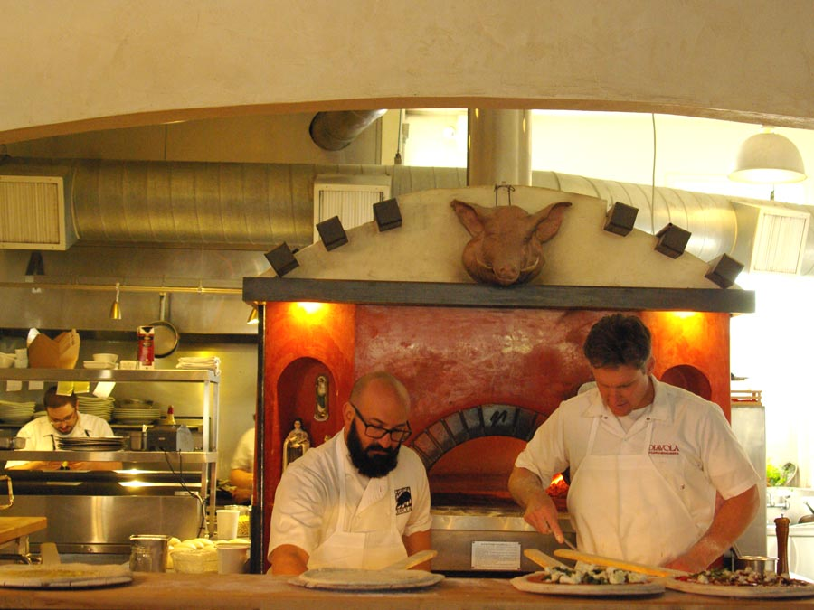 Chefs prepare pizza in front of a wood burning oven at Diavola Pizzeria & Salumeria, Geyserville