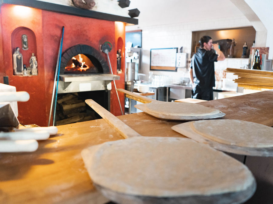 A chef stands next to the pizza oven where pizzass are ready to be cooked