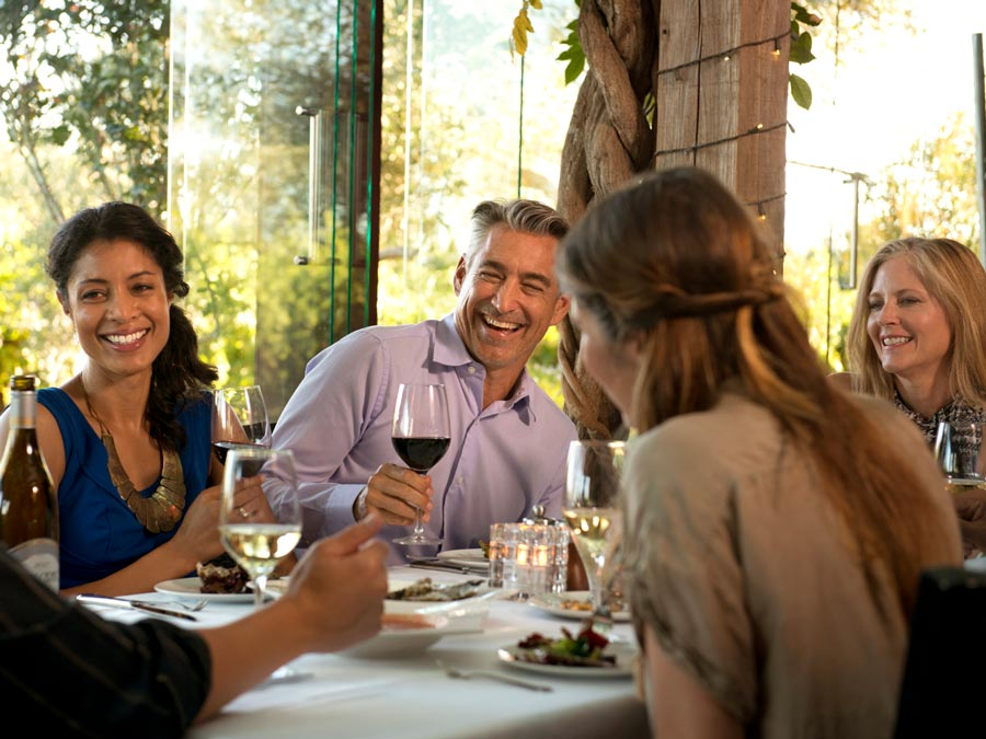 People smile and enjoy wine on a covered patio