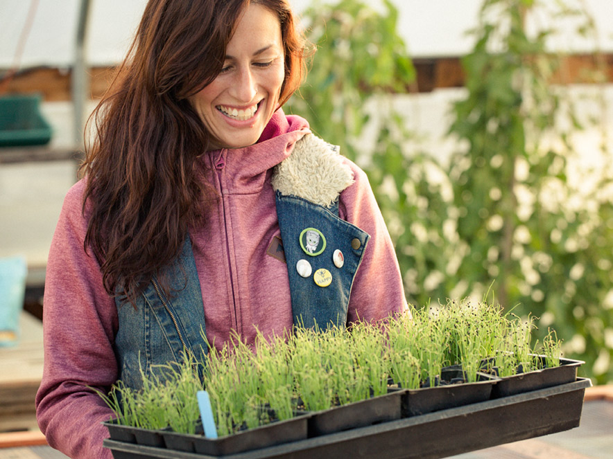 A farmer in a pink jacket and denim vest looks down at the plants she is holding inside of a greenhouse with a smile on her face