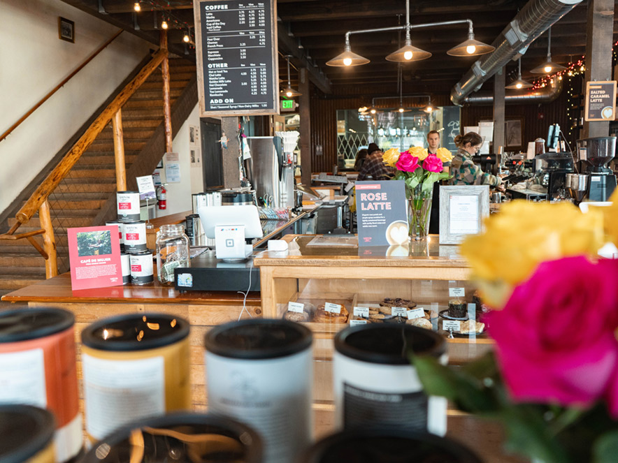 Flowers and coffee tins stand in the foreground of this shot of Taylor Lane Coffee's front counter in Sebastopol, Sonoma County, California