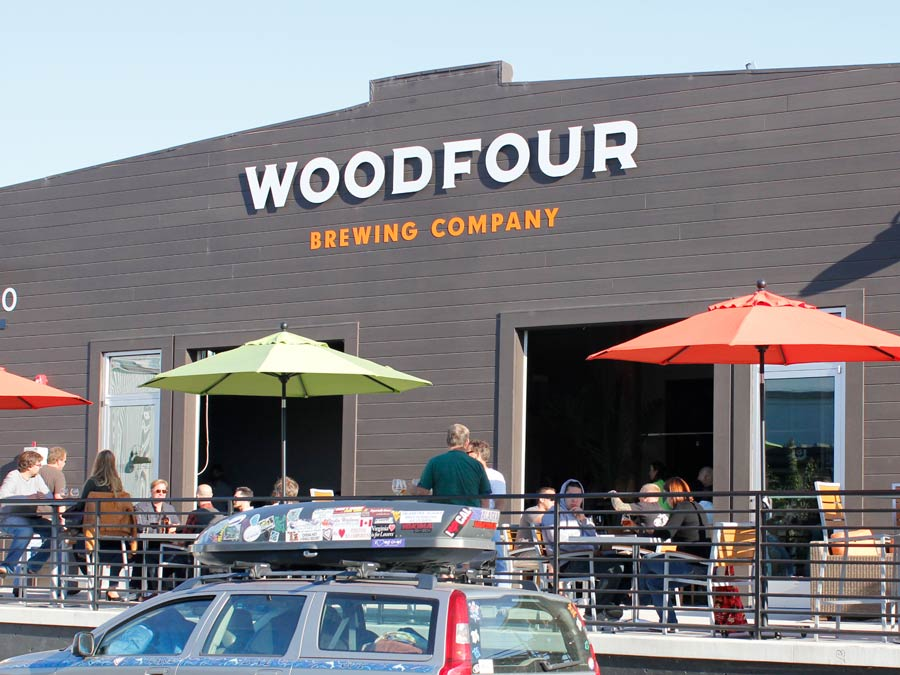 The patio in front of Woodfour Brewing has tables with colorful umbrellas in Sonoma County