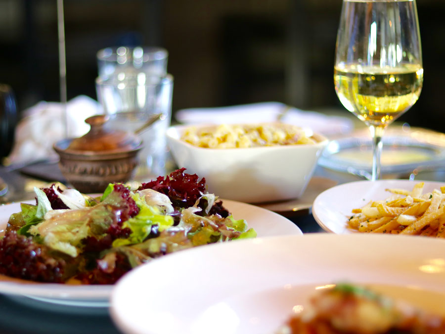 A beautiful, fresh salad sits alongside a glass of white wine at fig cafe & winebar, Glen Ellen