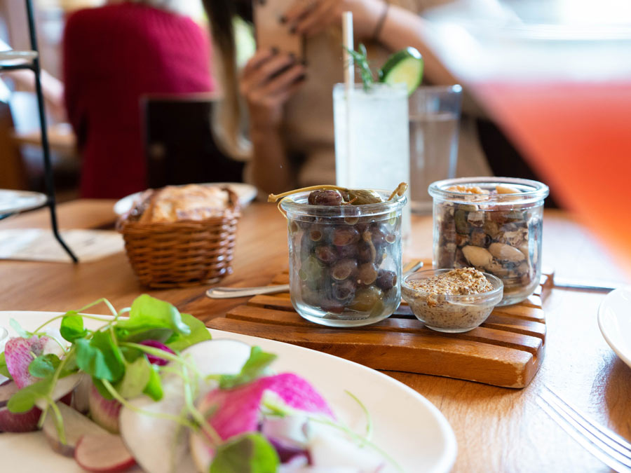 A salad with radishes and sprouts sits along side cups of nuts and a mojito at the girl & the fig in Sonoma County