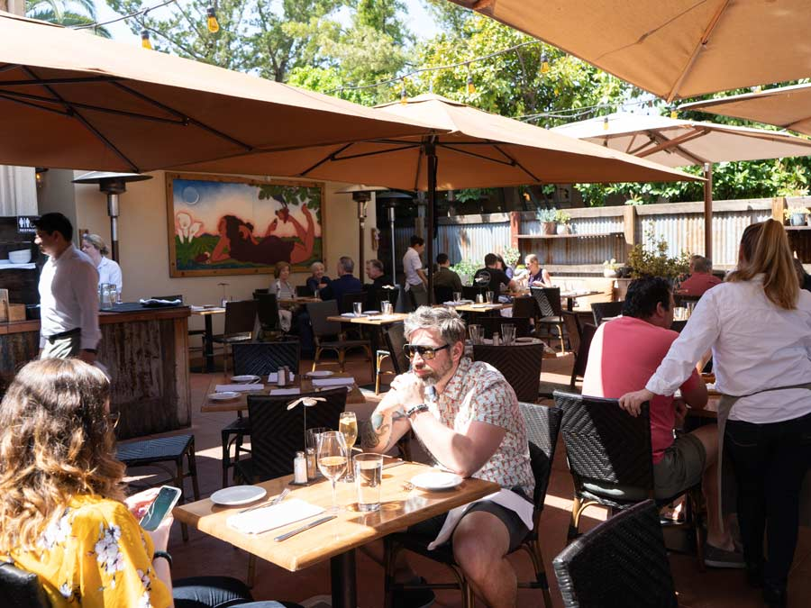 People enjoy the shade-covered patio at the girl & the fig