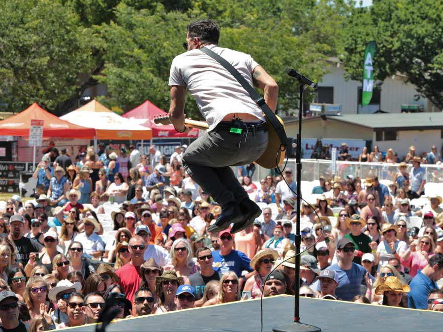 A performer jumps and plays guitar on stage at the Country Summer Music Festival, Sonoma County