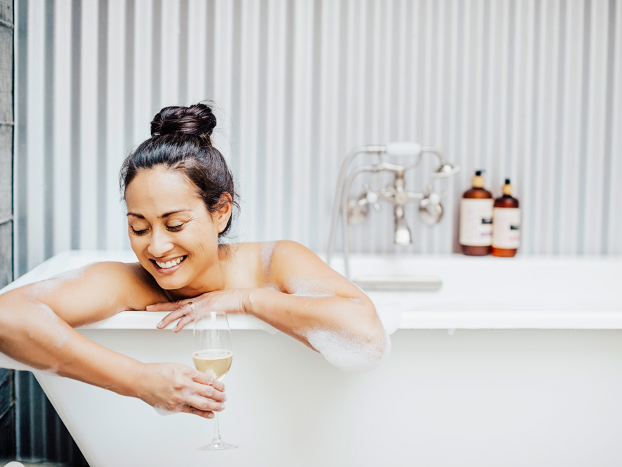 A woman soaks in a bubble bath with a glass of wine at the Farmhouse Inn & Restaurant, Forestville