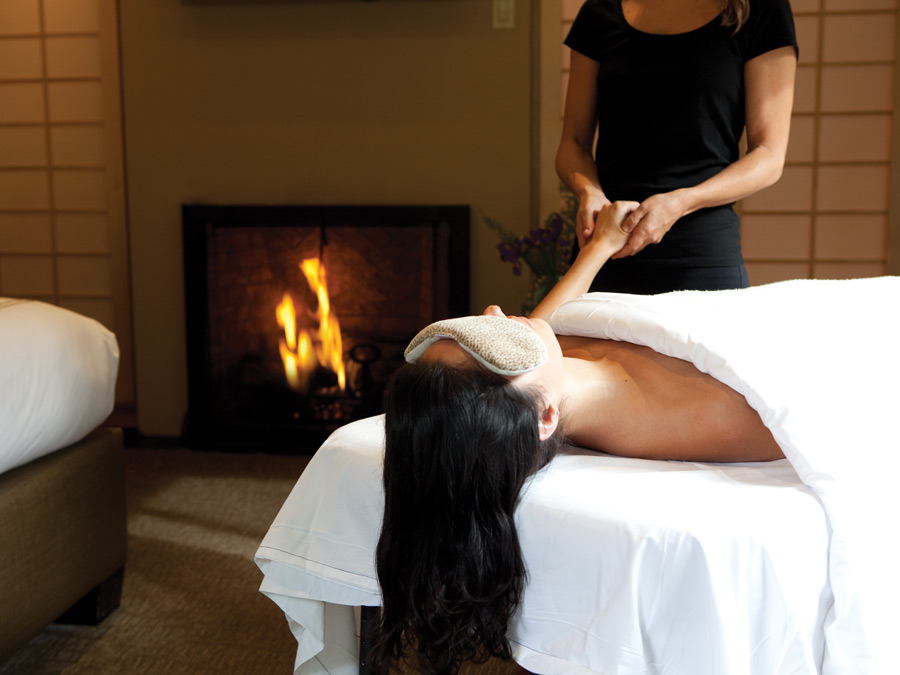 A woman gets a massage next to a fireplace at Gaige House + Ryokan, Sonoma County