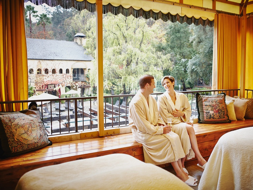 A couple sits on the balcony in white robes at the Kenwood Inn and Spa in Sonoma County, California