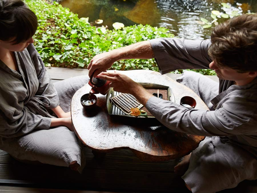 Two people in grey robes enjoy tea next to a garden