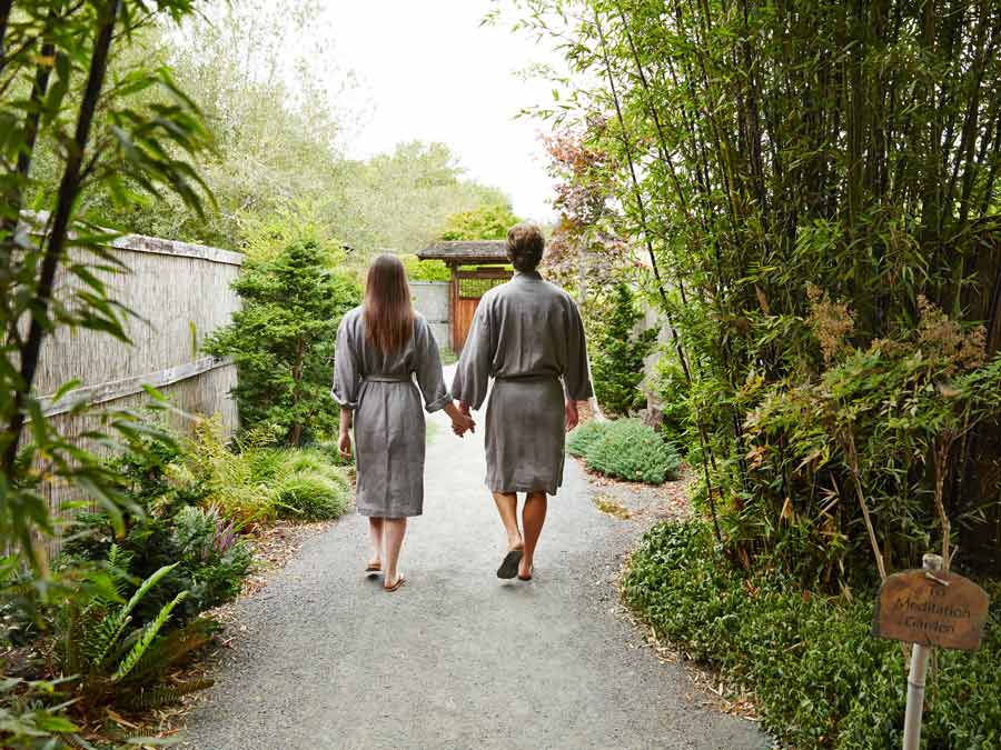 A couple walks down a bamboo-lined path toward the meditation garden at Osmosis Day Spa Sanctuary, Freestone
