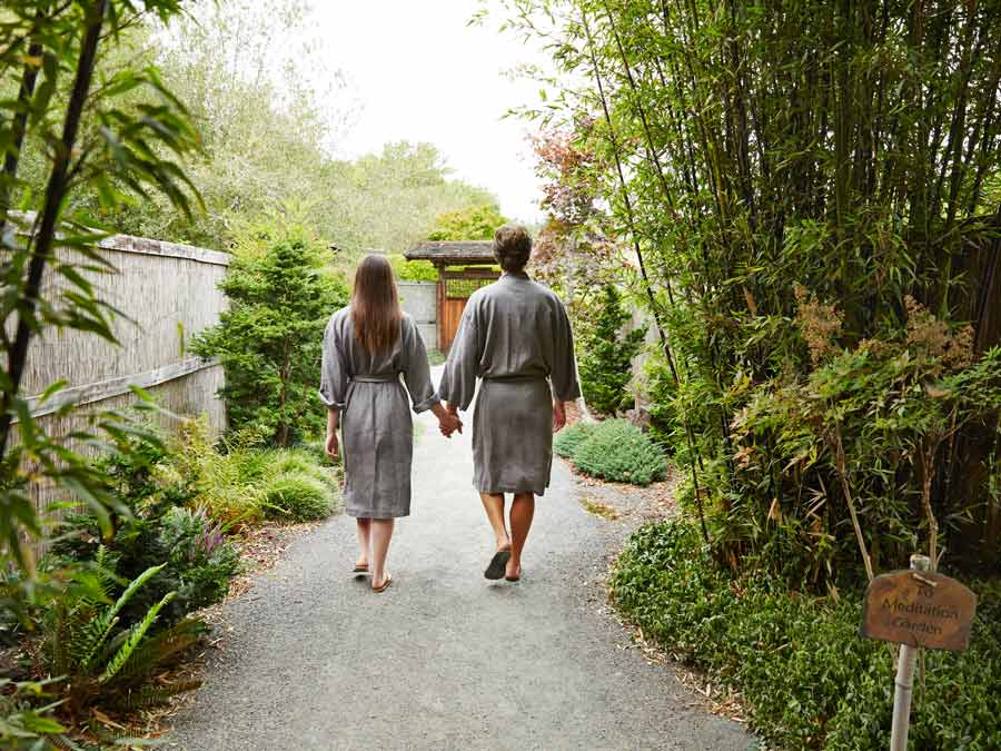 A couple walks down a bamboo-lined path at Osmosis Day Spa Sanctuary, Sonoma County