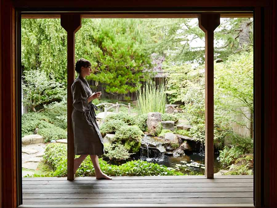 A woman drinks tea by the garden at Osmosis Day Spa Sanctuary, Sonoma County