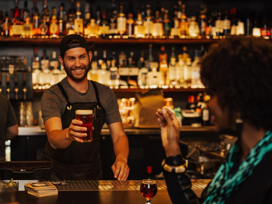 A woman is handed a beer by a smiling bartender in Sonoma County