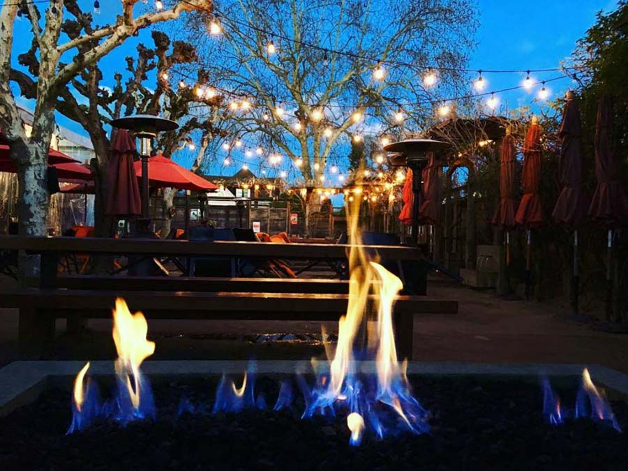A fire pit has a warm glow on the outdoor patio at HopMonk Tavern Sonoma in Sonoma County