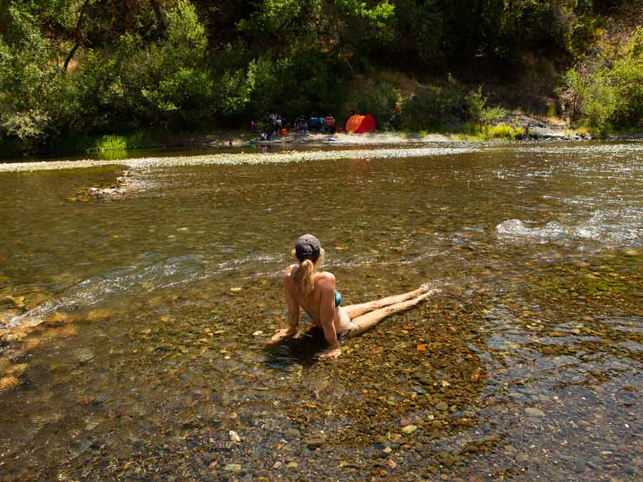 A woman lounges in the shallow water of the Russian River at Del Rio Woods, Sonoma County