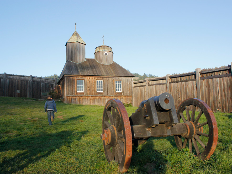 A person walks next to a cannon and a historic wood fence