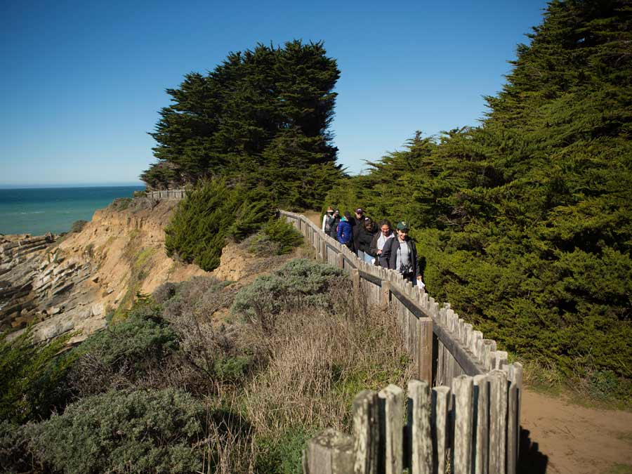 People hike down a path along the coast at Gualala Point Regional Park, Sonoma County