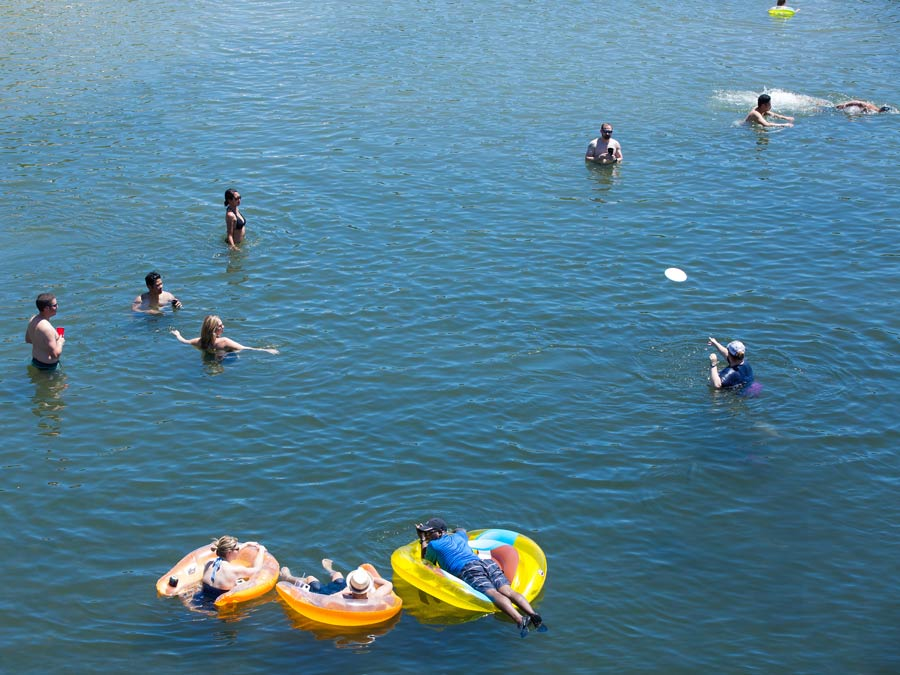 People float in inner tubes in the blue water of the Russian River at Healdsburg Veterans Memorial Beach regional park