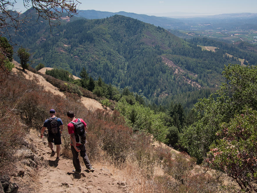 Two hikers trek down into a valley at Hood Mountain Regional Park, Sonoma County, CA