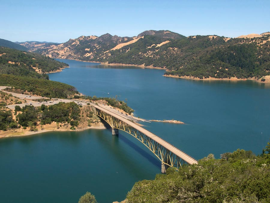 A bridge crosses the blue water of Lake Sonoma Recreation Area, Geyserville