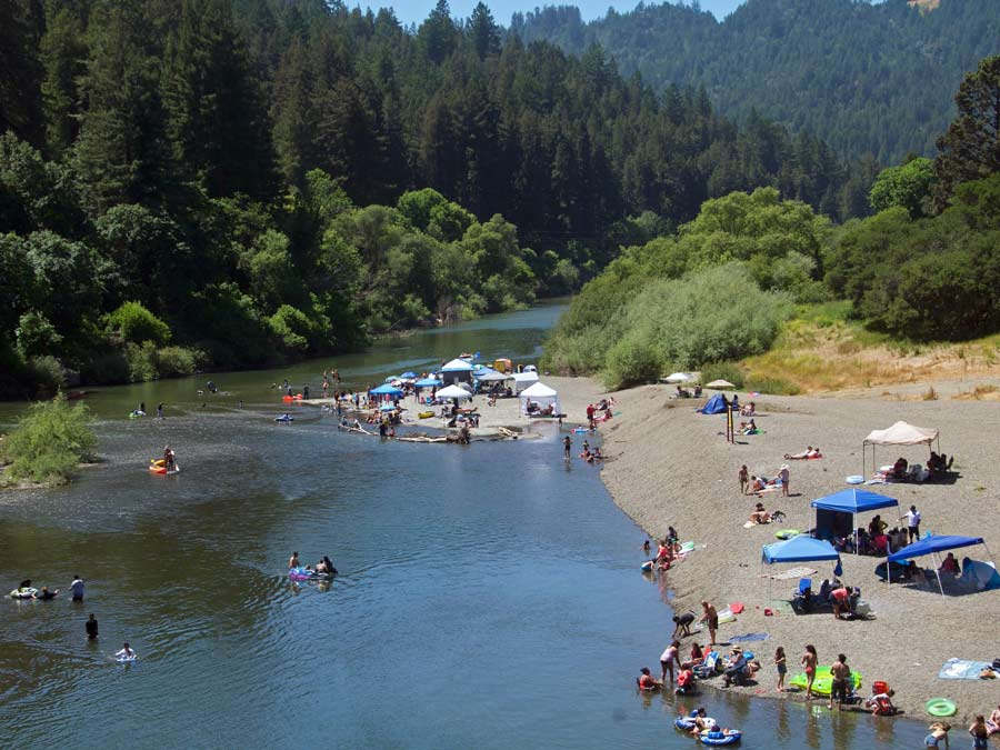 Trees surround the Russian River at Monte Rio Community Beach where people enjoy the water in Sonoma County
