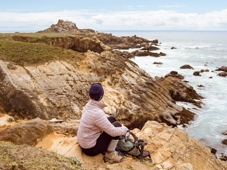 A woman sits on the edge of the coast and looks out over the Pacific Ocean