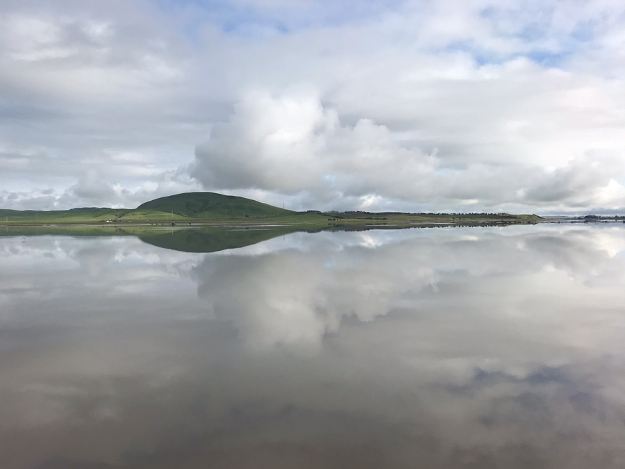 Clouds are reflected in the still water in the refuge