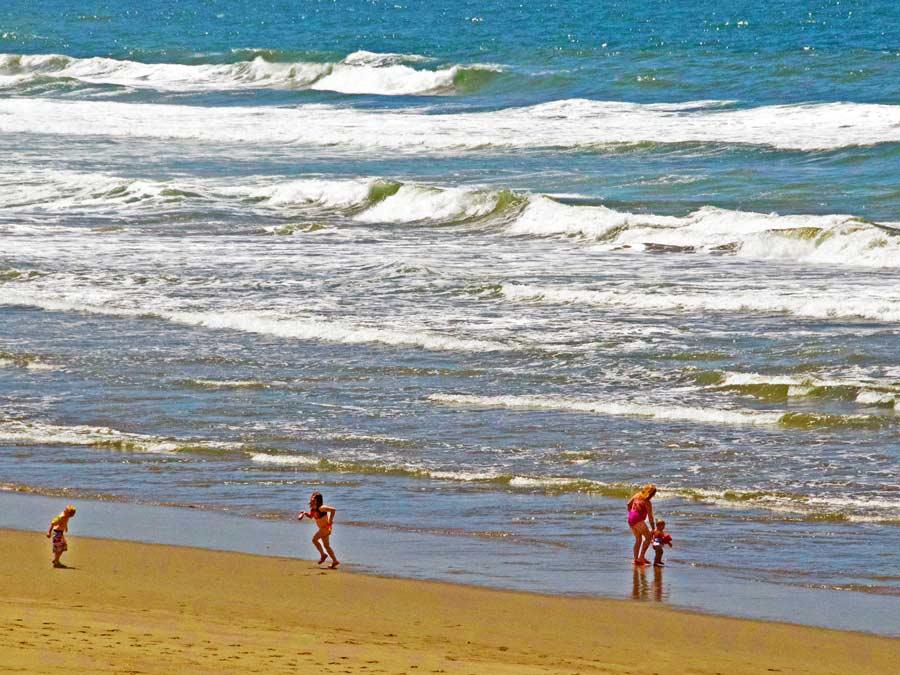 Personen planschen im Wasser vor der Küste von Sonoma County