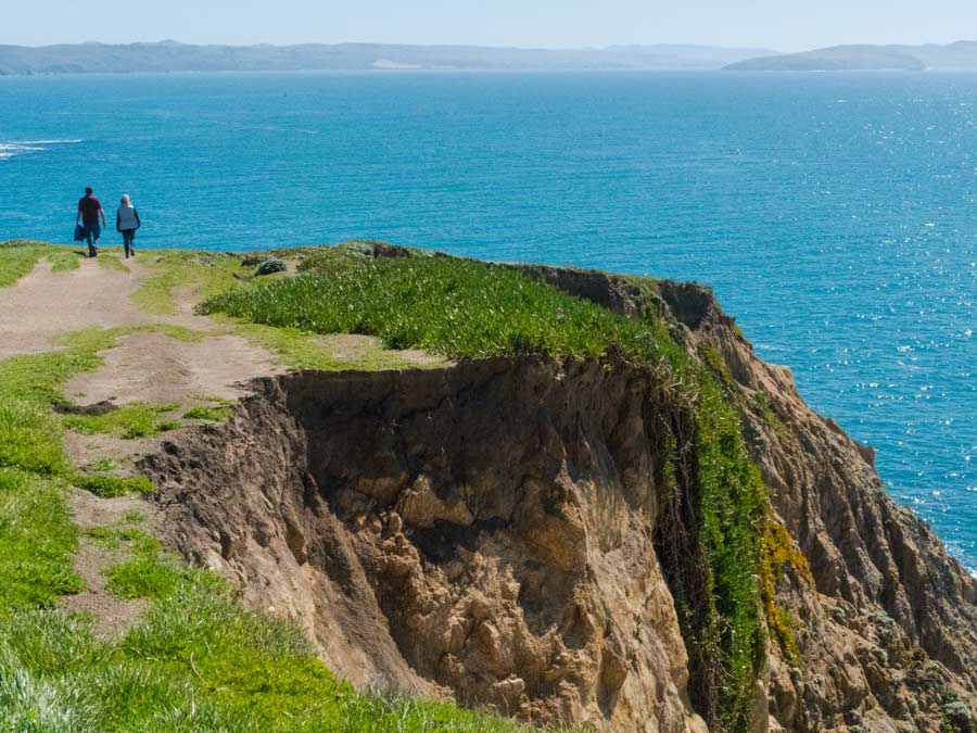A couple walks along the bluff top trail at Bodega Head, Sonoma County