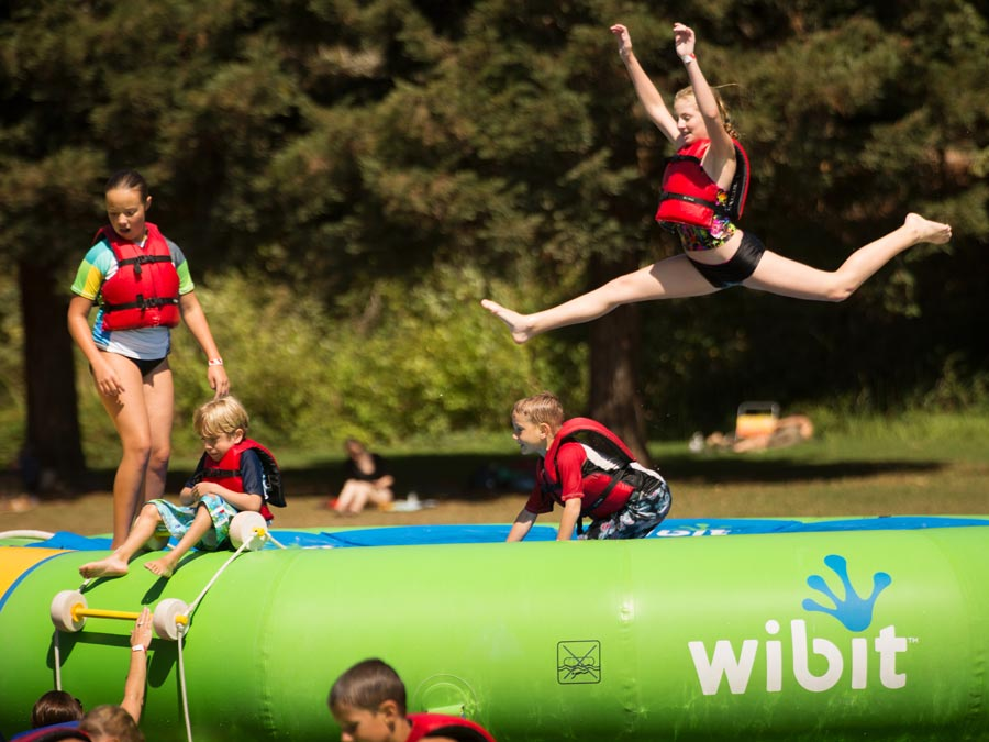 Kids jump on the inflatable water park at the swimming lagoon in Spring Lake Regional Park, Santa Rosa