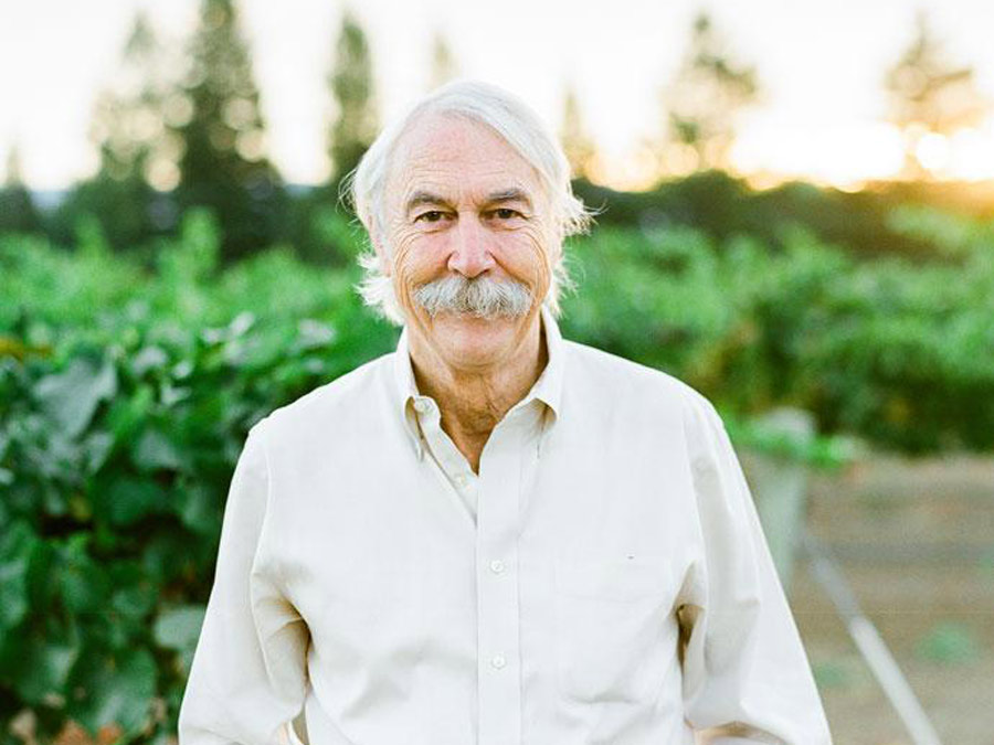 A man with a grey beard and mustache stands in front of green vineyards