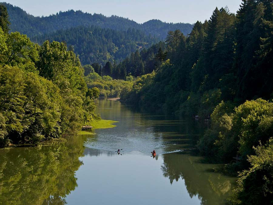 Two kayakers paddle down the Russian River in Sonoma County