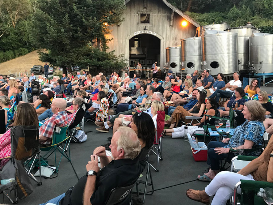 crowd of people sitting in lawn chairs at winery during comedy show in Sonoma County