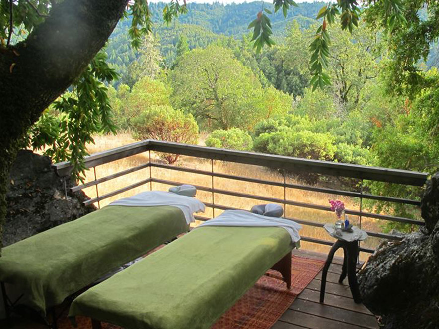 Two massage beds sit under a canopy of trees overlooking the mountain at Spa Gourmet in Sonoma County, California