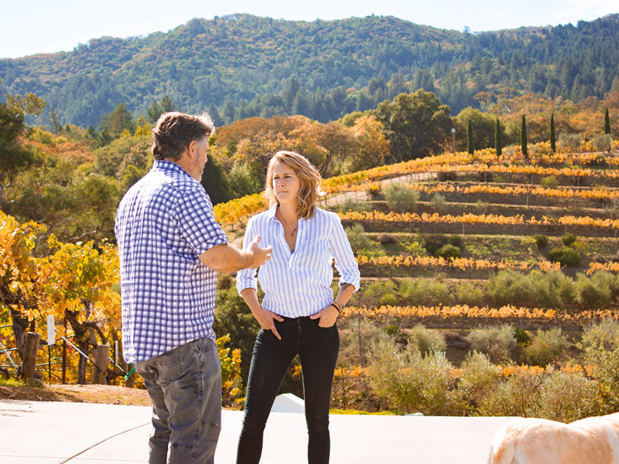 A winemaker explains wine concepts to a wine taster in the midst of orange vineyards at harvest time at Benziger Family Vineyards