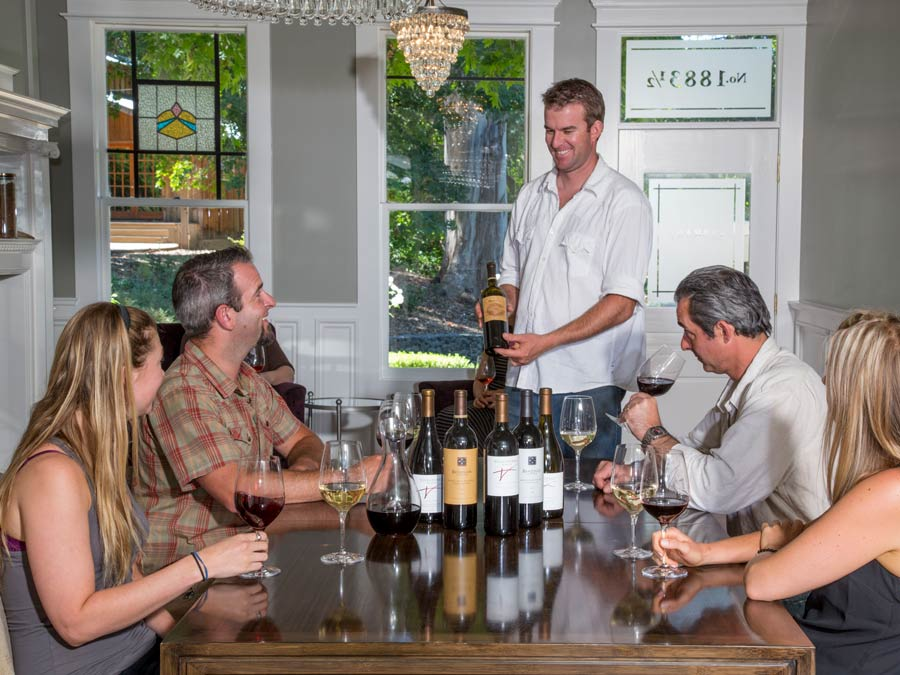 People sitting around the table with a wine educator from Benziger Family Winery, Glen Ellen