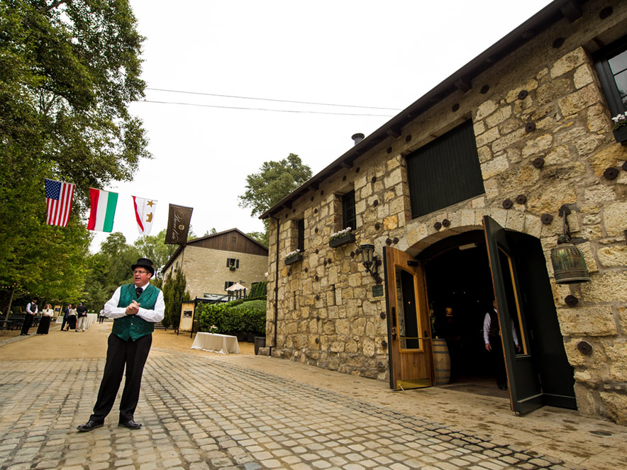 A person in historical dress gives a speech outside of a stone building at Buena Vista in Sonoma. Three flags wave in the distance.