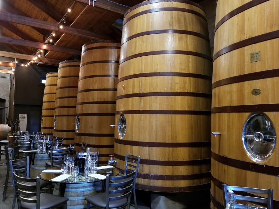 Tabes set up for tasting in the barrel room with big, wooden wine tanks at Dry Creek Vineyard, Healdsburg