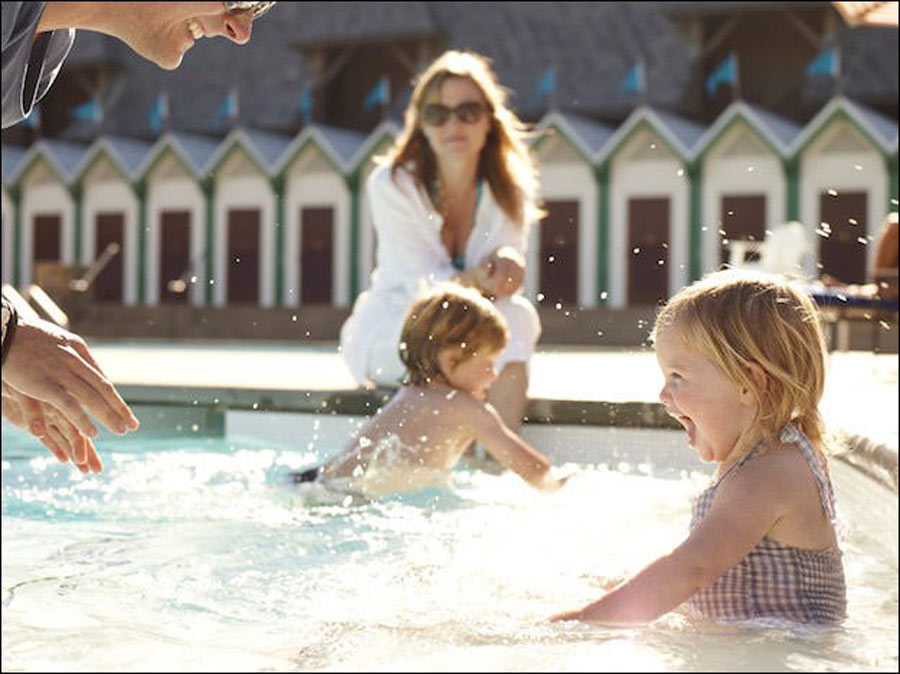 Two young children splash in the pool at Francis Ford Coppola Winery, Geyserville