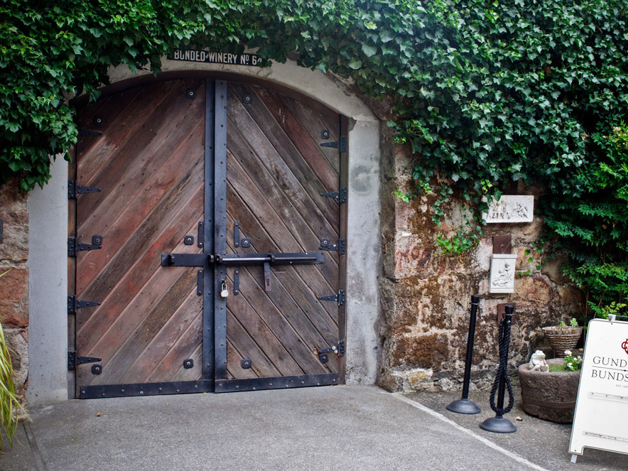 Heavy, wooden doors have ivy growing above them in Sonoma County