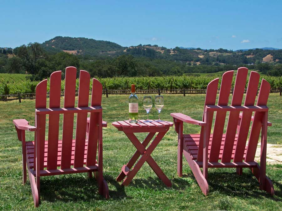 Two red adirondack chairs overlook the vineyard at Hanna Winery - Alexander Valley Hospitality Center, Sonoma County