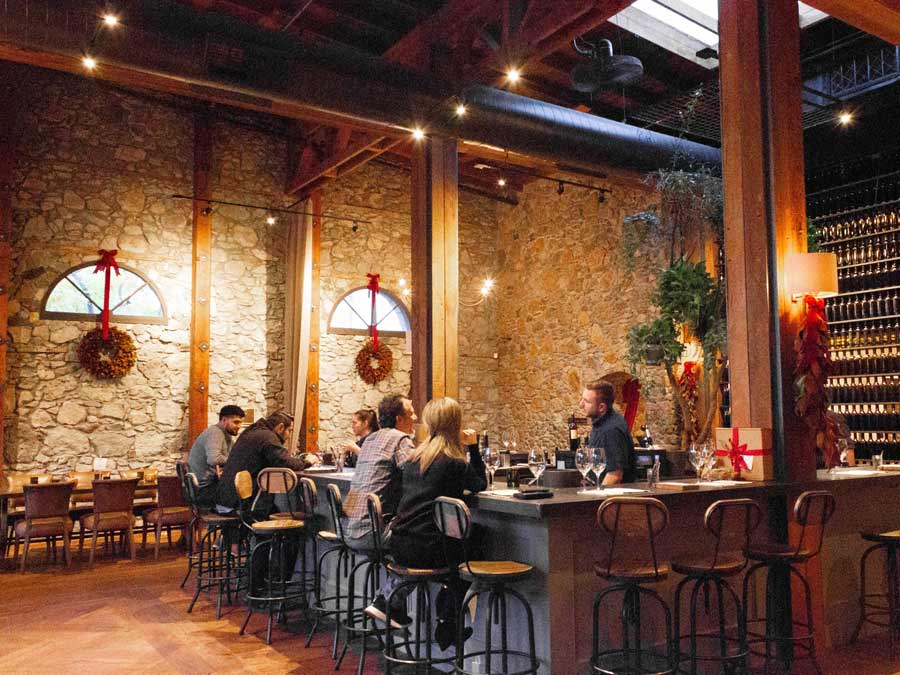 The interior of the swanky tasting room has high ceilings and stone walls